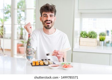 Young man eating asian sushi from home delivery screaming proud and celebrating victory and success very excited, cheering emotion