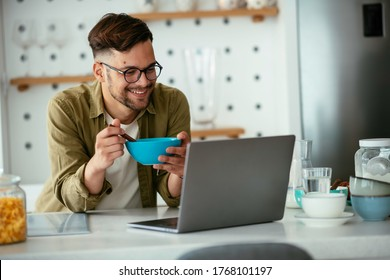 Young man eating breakfast and reading the news online. Handsome man enjoying at home.