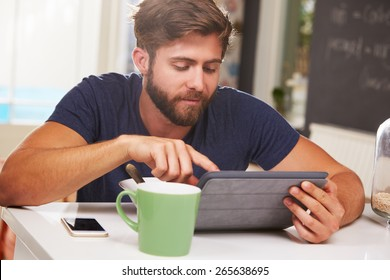 Young Man Eating Breakfast Whilst Using Digital Tablet