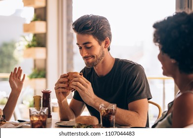 Young man eating burger while sitting with female friends at a restaurant. Man hanging out at cafe with friends and eating burger.