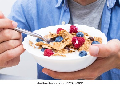young man eating cereal with fruit