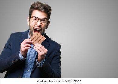young man eating a chocolate bar
