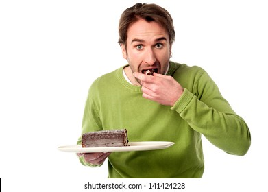 Young man eating chocolate cake in hurry