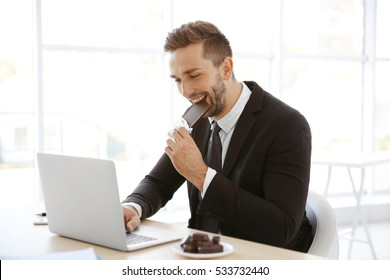 Young man eating chocolate while working with laptop in office