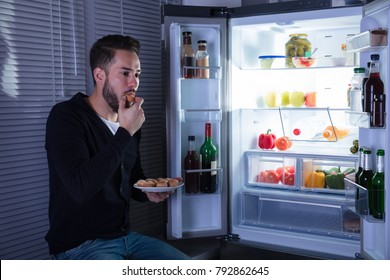 Young Man Eating Cookie In Kitchen Near Refrigerator