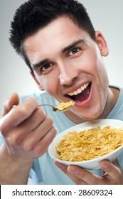 young man eating corn flakes close up