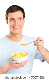 A young man eating cornflakes isolated on white background