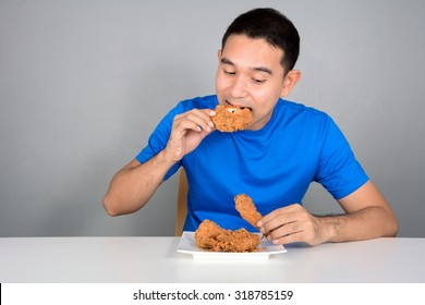 Young man eating fried chicken on the table