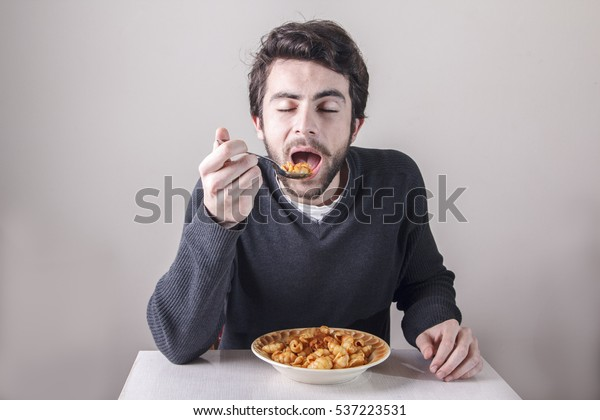 Young man eating his pasta food ravenously