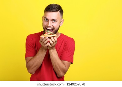 Young man eating pizza on yellow background