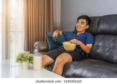 young man eating popcorn while sitting on a couch at home and watching TV