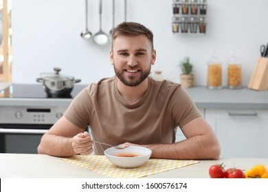 Young man eating tasty vegetable soup at table in kitchen