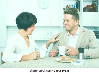 Young man and elderly woman have coffee sitting at table and communicate