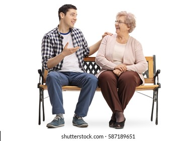 Young man and an elderly woman sitting on a bench and talking isolated on white background