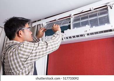 Young man electrician cleaning air conditioning in a client house