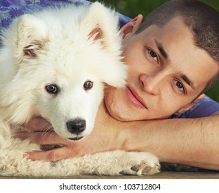 Young man embracing solid white fluffy little puppy dog