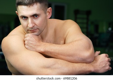 The young man is engaged in weightlifting in a gym and poses