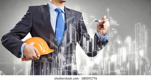 Young man engineer in helmet drawing construction project