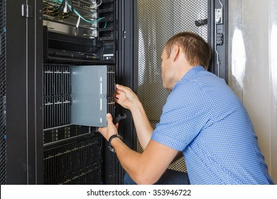 young man, IT engineer repair server in the data center