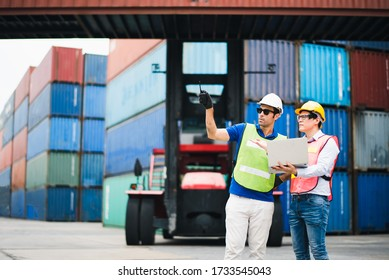 Young man Engineer and worker Check and control loading freight logistic Containers by use computer laptop at commercial shipping dock felling happy. Cargo freight ship import export concept