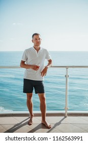 Young man enjoing life with glass of wine on a balcony at the seaside. Rich vacation concept