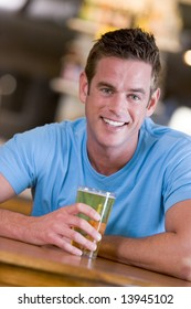 Young man enjoying a beer at a bar
