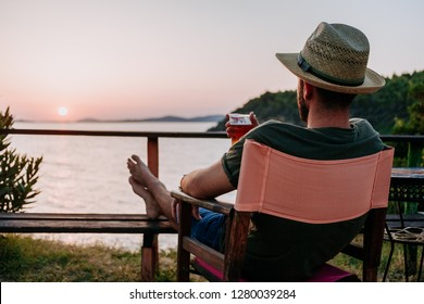 Young man enjoying beer and sunset in a beach bar