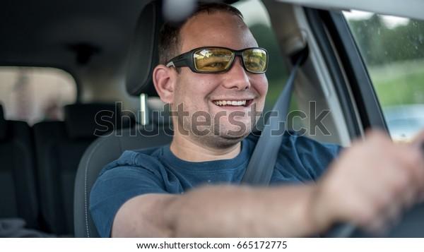 Young man enjoying car driving in sunglasses