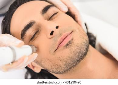 Young man enjoying cavitation facial peeling