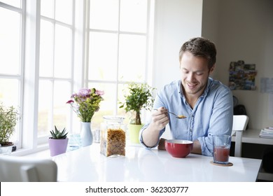 Young man enjoying eating breakfast