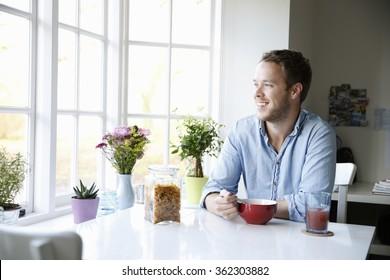 Young man enjoying eating breakfast