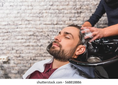 Young man enjoying hairwash at beauty salon