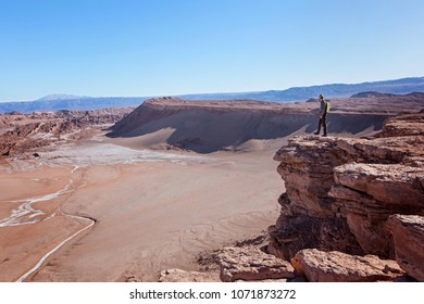 young man enjoying hiking and views at moon valley, valle de la luna, in atacama desert, chile, driest place on earth