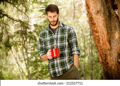 A young man enjoying a hot cup of coffee outside on a camping trip.