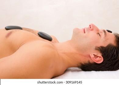 Young man enjoying a hot stone massage