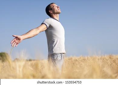 Young man enjoying life, his arms open