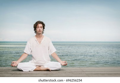 Young man enjoying meditation in Lotus position on the beach.