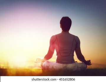Young man enjoying meditation and yoga on green grass on sunset sky background.