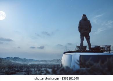 Young man enjoying a moonlit night on top of his camper van
