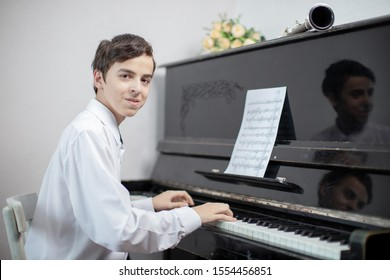 Young man enjoying playing an old nostalgic melody as he sits at an upright piano reading an old music score