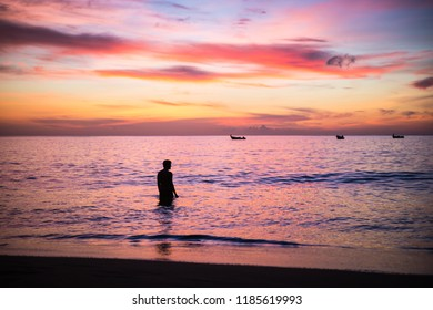 Young man enjoying a purple sky sunset in a calm sea in Caribe, Trinidad and Tobago, Caribe