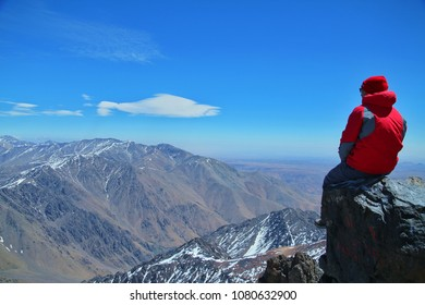 a young man enjoying a scenic view from the top of the Toubkal mountain, Morocco.