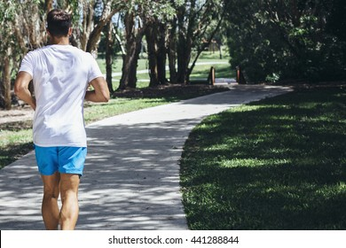 Young man enjoying a sunny afternoon run through a local park lined with over hanging trees and lush green grass.