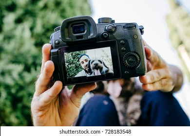 Young man enjoying a sunny day in the park with his brown dog. They are taking a picture together with the camera. Lifestyle