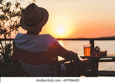 Young man enjoying sunset at a beach bar