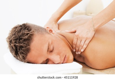 Young man enjoying the treatment in spa salon