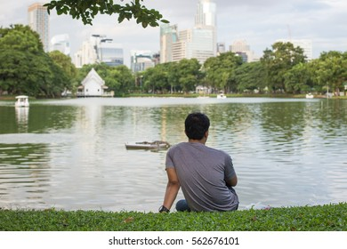 Young man enjoying the view of the lake in Lumpini park, Bangkok.