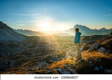 young man enjoying the view of the mountains landscape in the dolomites mountain range. tre cime di lavaredo national park, south tyrol