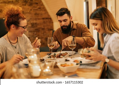 Young man enjoying while having dinner with his friends in dining room.