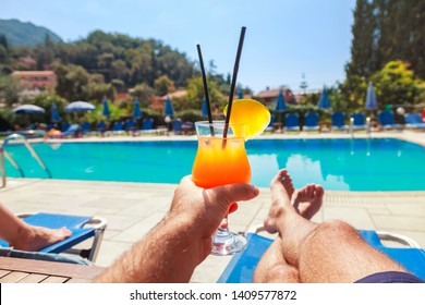 Young Man enjoying whit pineapple cocktail at the swimming pool. Man holding alcohol drink and lying on sunbed. Relax on Holidays